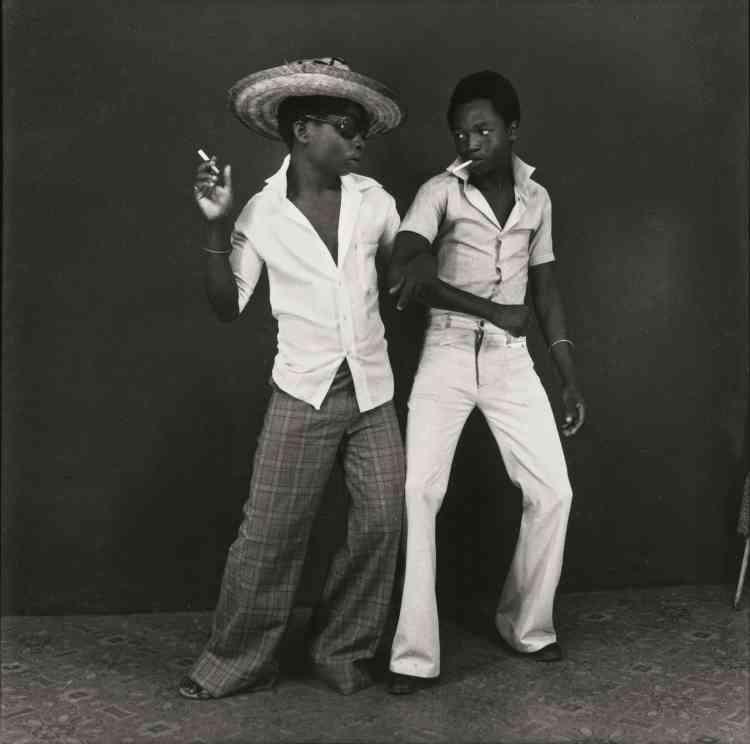 """""""Ambroise Ngaimoko a fui l'Angola en 1920. En 1968, il est assistant de son oncle qui lui offre son premier appareil photo. En 1971, il ouvre son propre studio, le Studio 3Z (pour les 3 Zaïres : le pays, la monnaie et le fleuve). Il y photographie principalement des jeunes tels que des athlètes aux biceps volumineux ou des sapeurs vêtus de leurs plus beaux habits."""""""