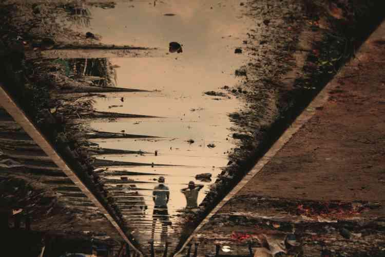 """""""Kiripi Katembo a étudié à l'Académie des Beaux arts de Kinshasa. Il a commencé à peindre puis à faire de la vidéo : il s'intéressera ensuite à l'image fixe. Dans cette série, intitulée """"Un Regard"""", il photographie la ville et ses habitants de façon poétique à travers ses flaques d'eau. """"Il y a une histoire derrière chaque photographie"""", confie-t-il. Ici, il inverse le sens de l'image en cherchant à ne retenir que le détail, le reflet."""""""