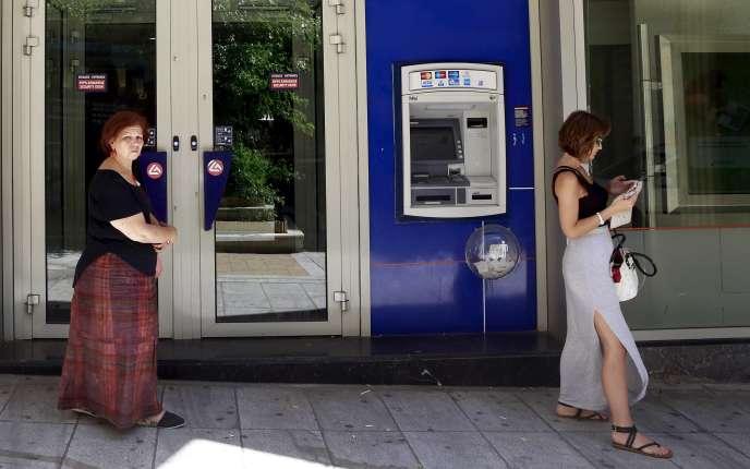 Devant un distributeur automatique de billets, à Athènes, le 8juillet.