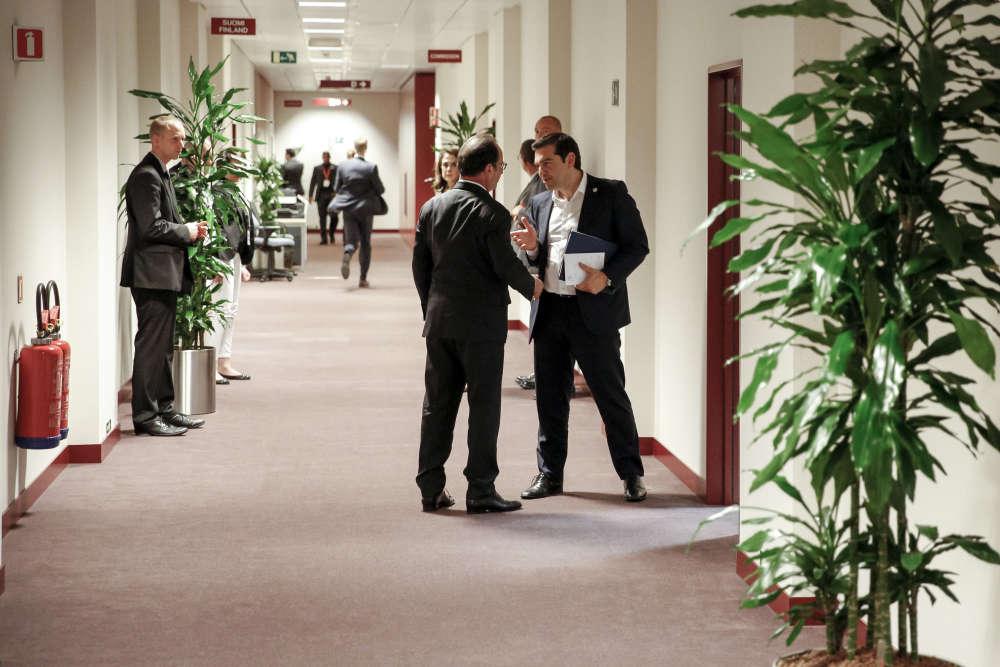 François Hollande et Aléxis Tsípras terminent leur discussion dans le couloir après s'être retrouvés dans les bureaux de la représentation de la France au siège de l'Union Européenne. Un nouveau sommet réunissant cette fois les 28 dirigeants européens se tiendra dimanche pour étudier les propositions d'Athènes, attendues avant vendredi matin.