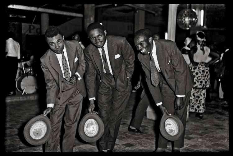 """""""Jean Depara est originaire d'Angola. Au début des années 1950, il s'installe à Kinshasa, métropole cosmopolite en pleine modernisation et découvre sa vie nocturne, animée par les rythmes de la rumba et du cha cha, en fréquentant les bars et les boîtes de nuits à la mode. Il capture les gens sur le vif dans la rue ou à la sortie des boîtes de nuit, des danseurs et des musiciens."""""""