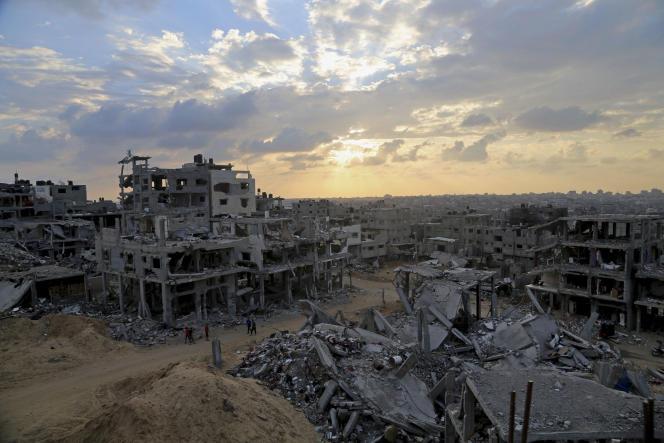 Des Palestiniens cheminent entre les ruines d'un bâtiment détruit dans le quartier de Shijaiyah, à Gaza, le 12 octobre 2014.