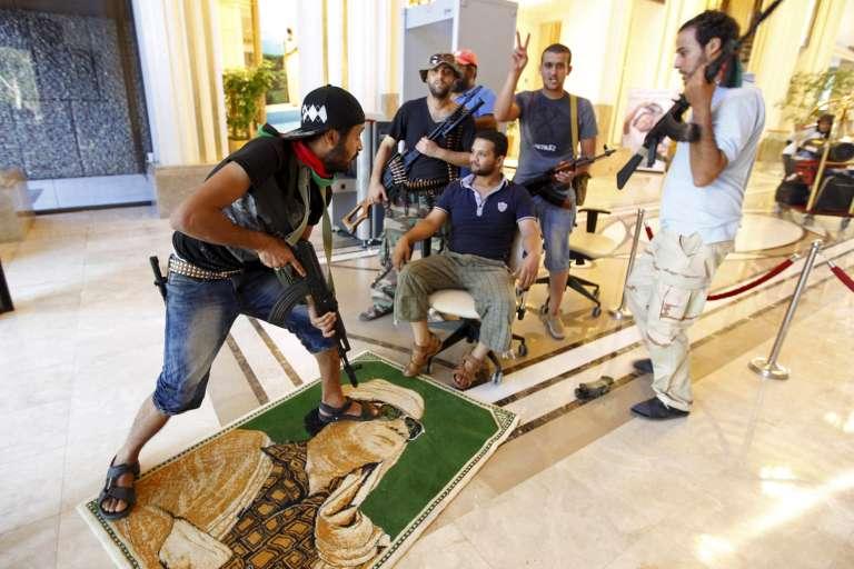 Des rebelles piétinent l'image de Mouammar Kadhafi, à Tripoli, le 24 août 2011.