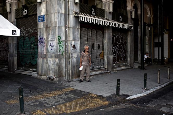 Un homme devant des boutiques fermées au matin du 7 juillet 2015 à Athènes.