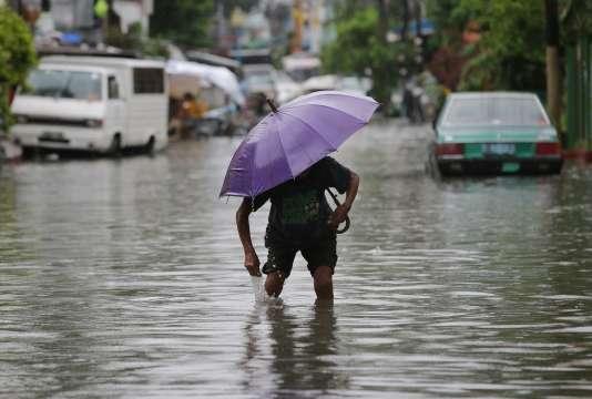 Un homme dans les rues de Quezon , au nord de Manille, aux Philippines, le jeudi 9 juillet 2015. Les fortes pluies du typhon Chan-Hom ont intensifié la mousson saisonnière.