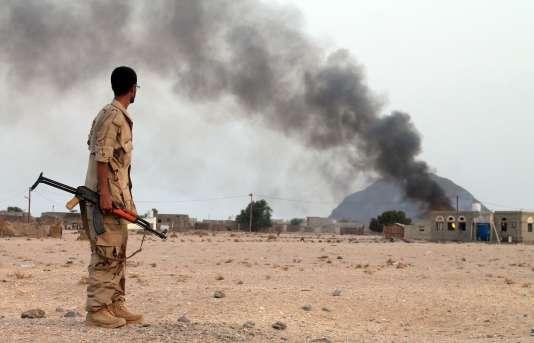 Un soldat yéménite regarde la fumée s'échapper d'un immeuble après une attaque des rebelles houthistes à Aden, dimanche12juillet.