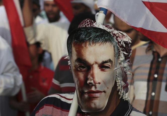 Un manifestant pro-démocratie porte un masque à l'effigie de Nabil Rajab à Abu Saiba, à l'ouest de la capitale du Bahreïn, Manama, en mars 2014.