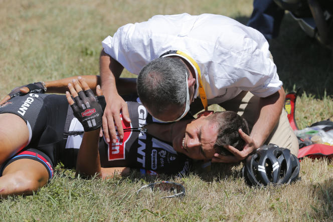 A medic tends to Warren Barguil of France who crashed during the tenth stage of the Tour de France cycling race over 167 kilometers (103.8 miles) with start in Tarbes and finish in La Pierre-Saint-Martin, France, Tuesday, July 14, 2015. (AP Photo/Christophe Ena)