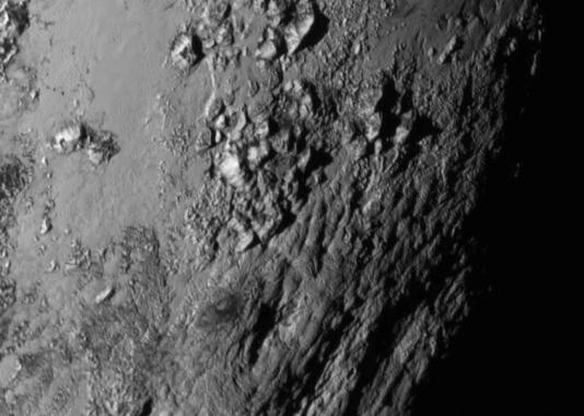 Gros plan pris par la sonde New Horizons d'une région de Pluton proche de l'équateur révélant des montagnes de glace hautes de 3500 mètres.