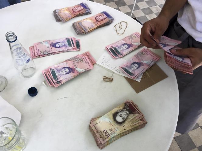 Un serveur compte des bolivars donnés par quatre clients pour payer leur déjeuner, à Caracas, le 14 juillet 2015.