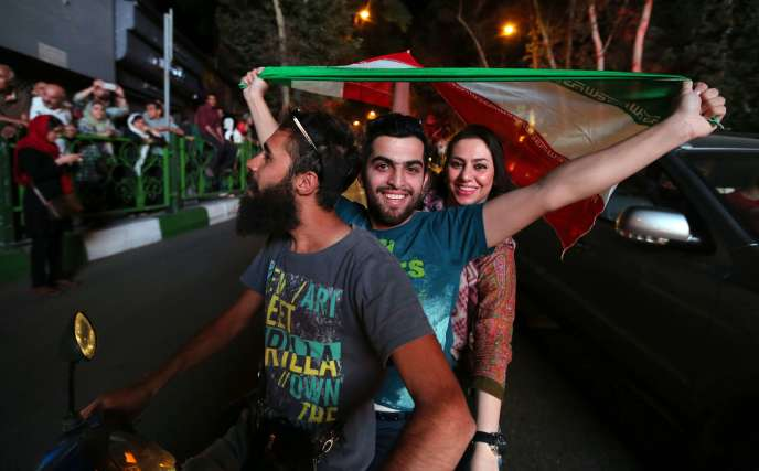 Des Iraniens agitent le drapeau lors des célébrations à Téhéran, le 14 juillet 2015.