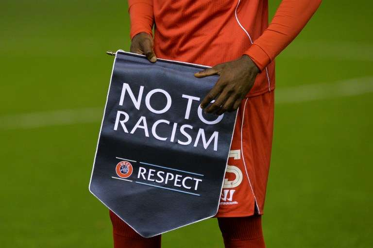 """L'Italien Mario Balotelli tient un fanion """"Non au racisme"""", en 2014 à Liverpool."""