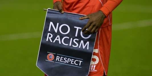 L'attaquant italien Mario Balotelli tient une pancarte «Non au racisme. Respect».