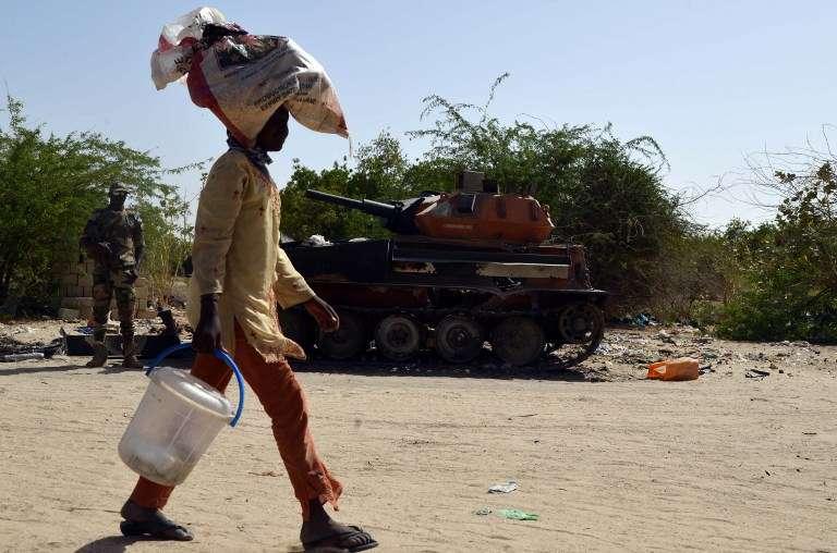 A la frontière du Niger et du Tchad, un homme passe devant un ancien tank de Boko Haram, en mai 2015.