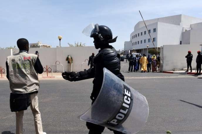 Un policier tente d'empêcher un journaliste de prendre des photos, à Dakar en mars 2015.