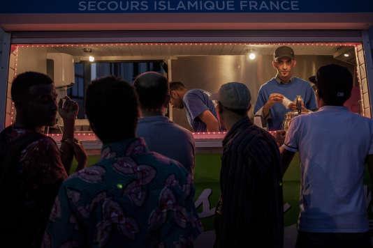 Des bénévoles offrent le thé dans un camion garé en face de la tente des Tables du ramadan, le 17 juillet.