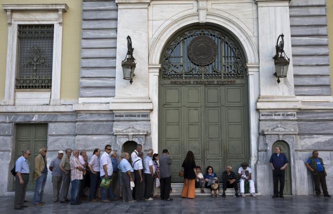 Des Grecs patientent devant la Banque nationale de Grèce, en juillet 2015. Celle-ci a été fermée pendant près de trois semaines.