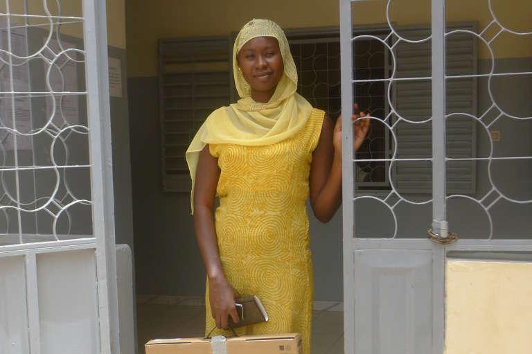 Serigne Saliou Diop reçoit  son ordinateur pour pouvoir commencer ses cours à l'Université Virtuelle du Sénégal, le 2 juillet à Mbour, au sud de Dakar. Un an s'est écoulé depuis qu'elle a obtenu son baccalauréat en juillet 2014.