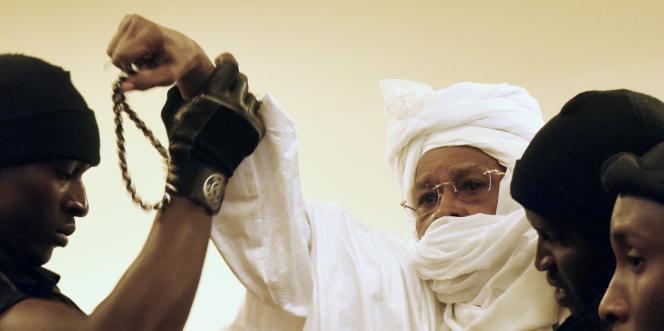 Hissène Habré, entouré de gardiens de prison qui l'amène devant les Chambres africaines extraordinaires où il est jugé, le 20 juillet