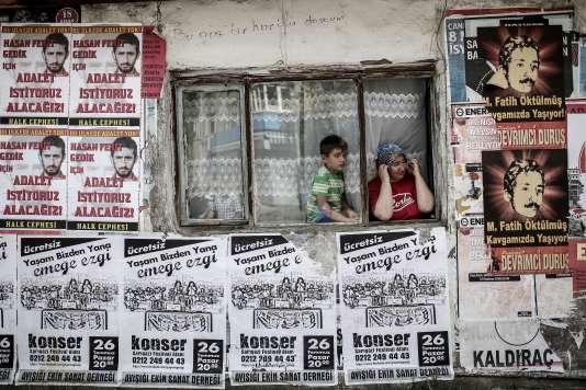 A Istanbul, le 22 juillet, une mère et son fils observent le cortège d'enterrement de trois activistes tués dans un attentat à Suruç, deux jours plus tôt.