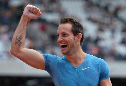 Renaud Lavillenie, anneaux olympiques tatoués sur le bras, célèbre sa victoire dans le concours de la perche à Londres, le 25 juillet 2015 .