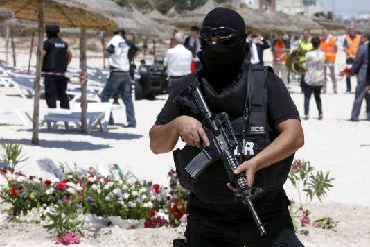 Un membre des forces de sécurité tunisiennes monte la garde le 29 juin 2015 sur le site de l'attaque terroriste qui a fait 38 morts sur une plage de Sousse.