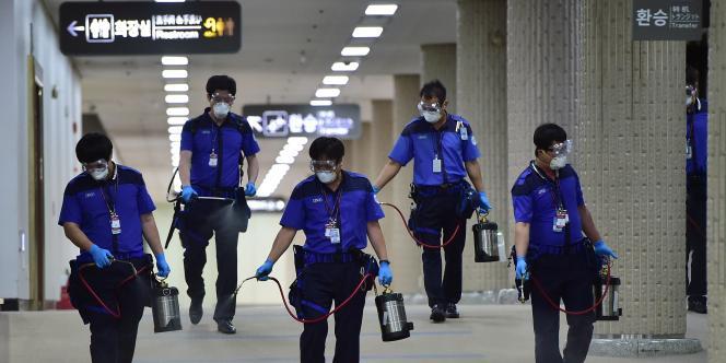Des employés désinfectent des couloirs de l'aéroport international de Gimpo à Séoul, le 17 juin.