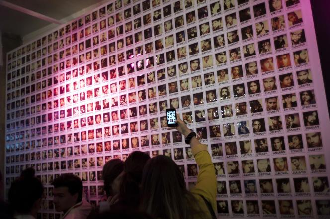 Une femme devant un mur de photos d'hommes disponibles lors de la soirée d'ouverture de la boutique du site de rencontre