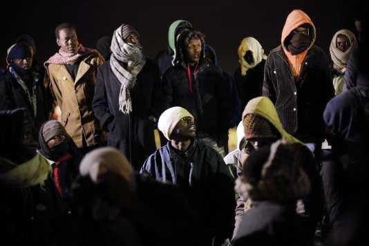 Des migrants interpellés par la police dans la zone du tunnel, à Calais, jeudi 30 juillet.