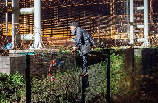 Un migrant passe au-dessus d'une barrière à Coquelles, le 30 juillet.