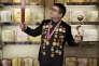 """Chen Guangbiao, entrepreneur et philantropiste dans les bureaux de sa société entouré des """"diplômes"""" et couvert de médailles, offerts pour le remercier de sa générosité. Nanjing  le 19 juin 2015."""