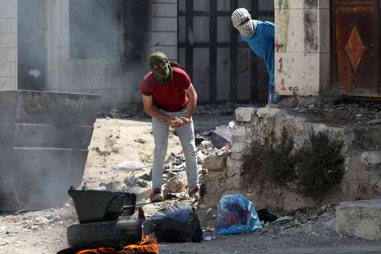 Des Palestiniens prêts à jeter des pierres à Hebron.