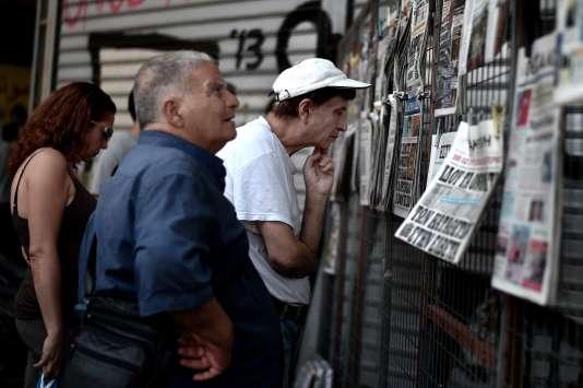 Des Grecs lisent les titres de la presse à Athènes, le 31 juillet.
