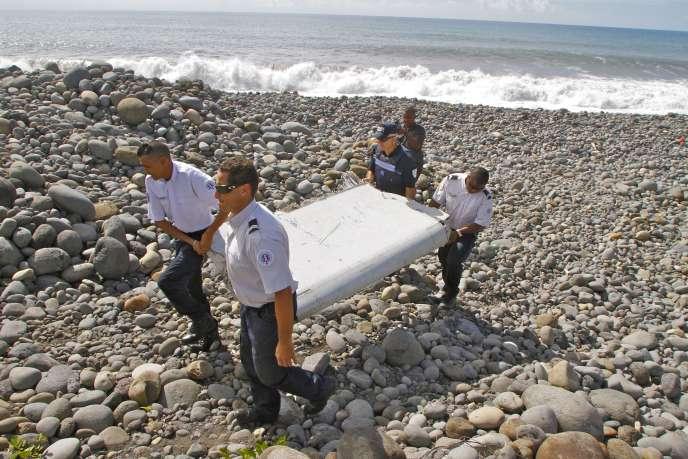 Des gendarmes transportent un fragment d'aile d'avion retrouvé sur une plage de La Réunion, mercredi 29juillet.