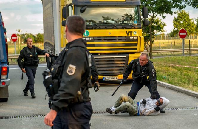 Des gendarmes français stoppent un migrant qui voulait rejoindre le Royaume-Uni, à Coquelles, près de Calais, le 30 juillet.