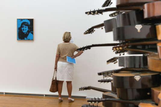 """Une visiteuse au Musée de Grenoble avec, à gauche, """"Jackie"""" (1964), d'Andy Warhol et, à droite, """"Allegro con brio"""" (1977) d'Arman."""