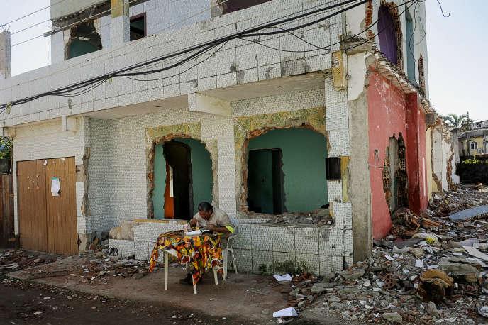 Un ouvrier travaillant à la construction du site olympique prend son déjeuner au milieu des maisons détruites de la Vila Autodromo, dans la zone ouest de Rio de Janeiro, le 11 juillet.
