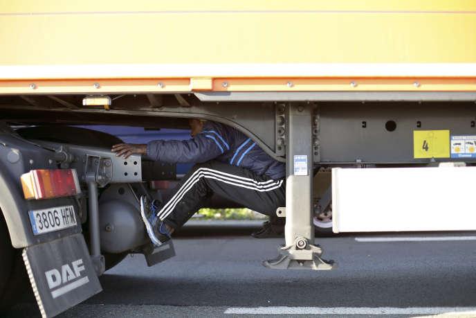 Caché sous la remorque d'un camion, un migrant tente de passer la frontière avec le Royaume-Uni, le 24 juin, à Calais.