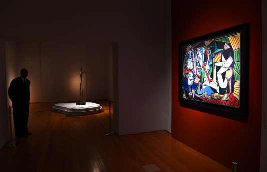 """Le tableau """"Les femmes d'Alger"""" de Pablo Picasso a été vendu aux enchères en mai 2015 à New York pour 179,4 millions de dollars, devenant l'œuvre d'art la plus chère au monde. En arrière-plan, la sculpture """"L'homme au doigt"""" d'Alberto Giacometti."""