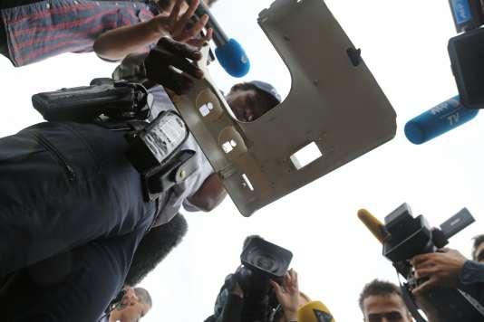 Des journalistes autour d'un policier tenant une pièce en plastique trouvée sur un rivage de Saint-Denis, sur l'île de la Réunion, le 4 août.