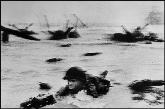 """""""Face in the Surf"""", la plus célèbre photo du Débarquement prise par Capa. Le soldat, identifié comme Huston Riley, a d'ailleurs raconté en 2004 avoir été aidé par Robert Capa."""