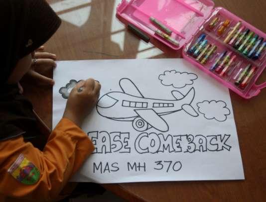 Une enfant indonésienne dessine l'avion de la Malaysia Airlines.