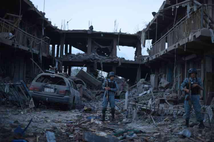 Photo prise le 7 août 2015 : un policier afghan sur les décombres d'un marché, détruit par une attaque à la bombe qui avait tué au moins sept personnes.