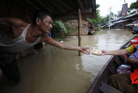 A Nyaung Tone en Birmanie, dans le delta d'Irrawaddy, au sud-ouest de Rangoun, un homme sinistré reçoit de l'aide alimentaire dans sa maison en grande partie submergée, le 7 août 2015.