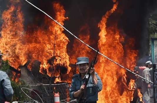 Un policier afghan devant la voiture piégée en flammes près de l'aéroport de Kaboul, lundi 10 août.