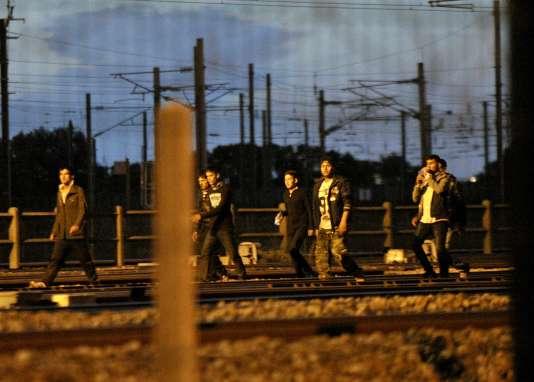 Des migrants marchent le long des rails près de la gare de Calais-Fréthun, le 10 août.