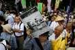 «La guerre est finie», affirme un manifestant sur sa pancarte, lors d'un rassemblement contre les projets du premier ministre devant le Parlement, à Tokyo, le 15juillet.