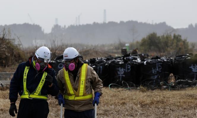 Des hommes en combinaison de protection contre la radioactivité travaillent à la décontamination d'une zone dévastée par la catastrophe nucléaire, à Namie, préfecture de Fukushima, en février.