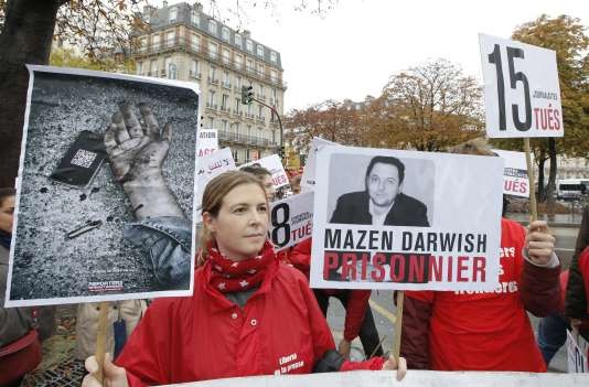 Des membres de Reporters sans frontières brandissent le portrait de Mazen Darwich, lors d'une manifestation contre la violence en Syrie, le 20octobre2012 à Paris.