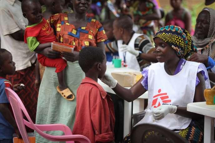 Marguerite, agent de santé de Médecins sans frontières, fait avaler un cachet contre le paludisme à un enfant.